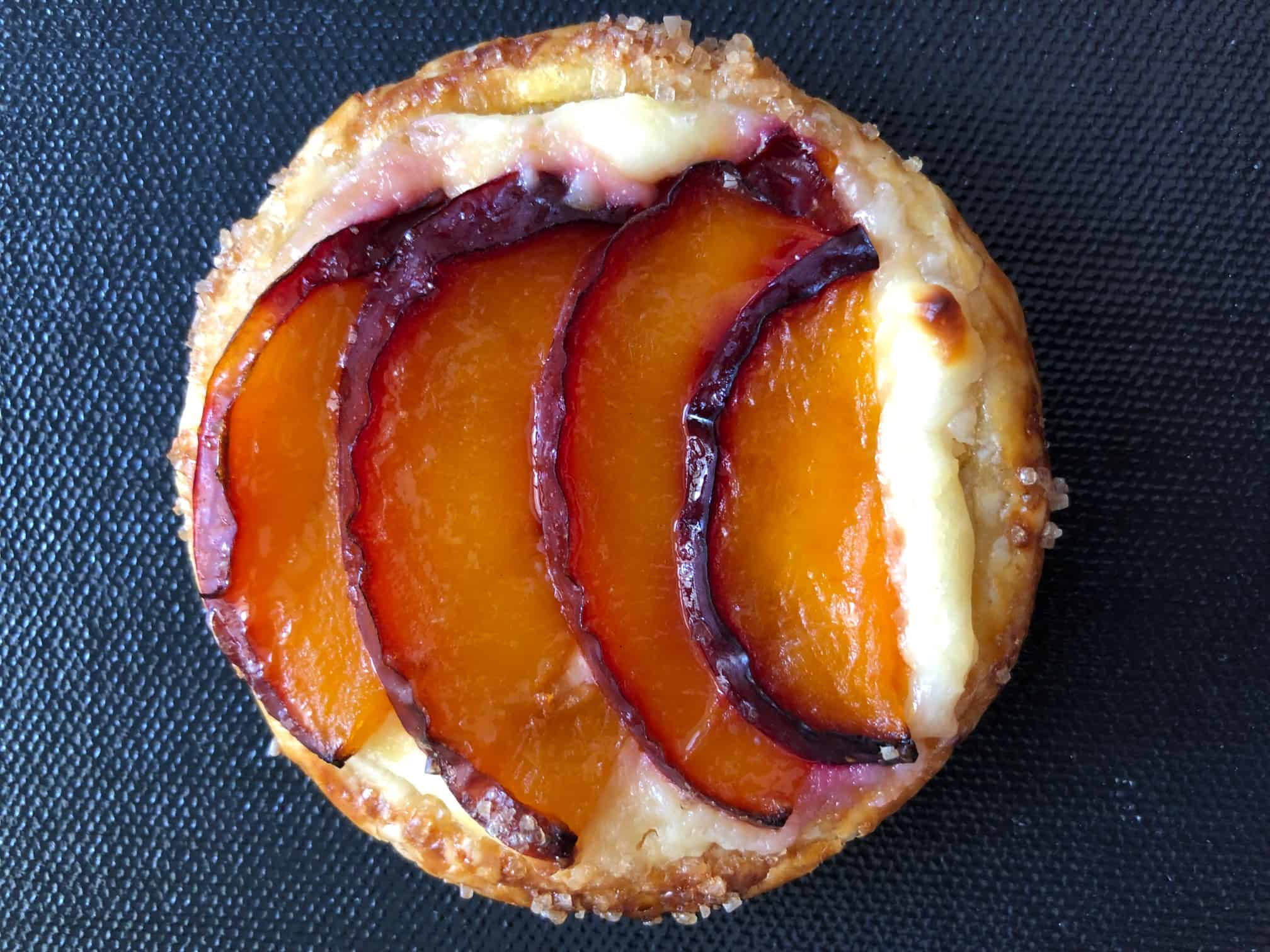 Close up of a mini plum tartlet on a gray background