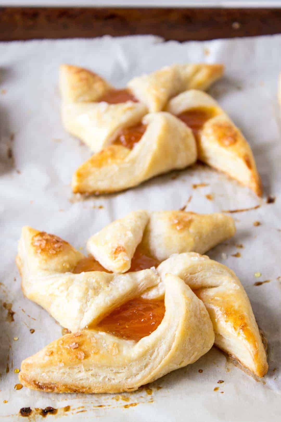 Close up of 2 puff pastry pinwheels filled with jam on a piece of parchment paper