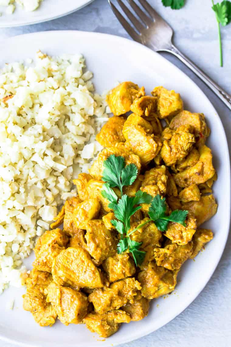 Close up of vadouvan curry chicken on  a white plate with cauliflower rice and a second plate, fork, and cilantro leaves in the background. all over a white background