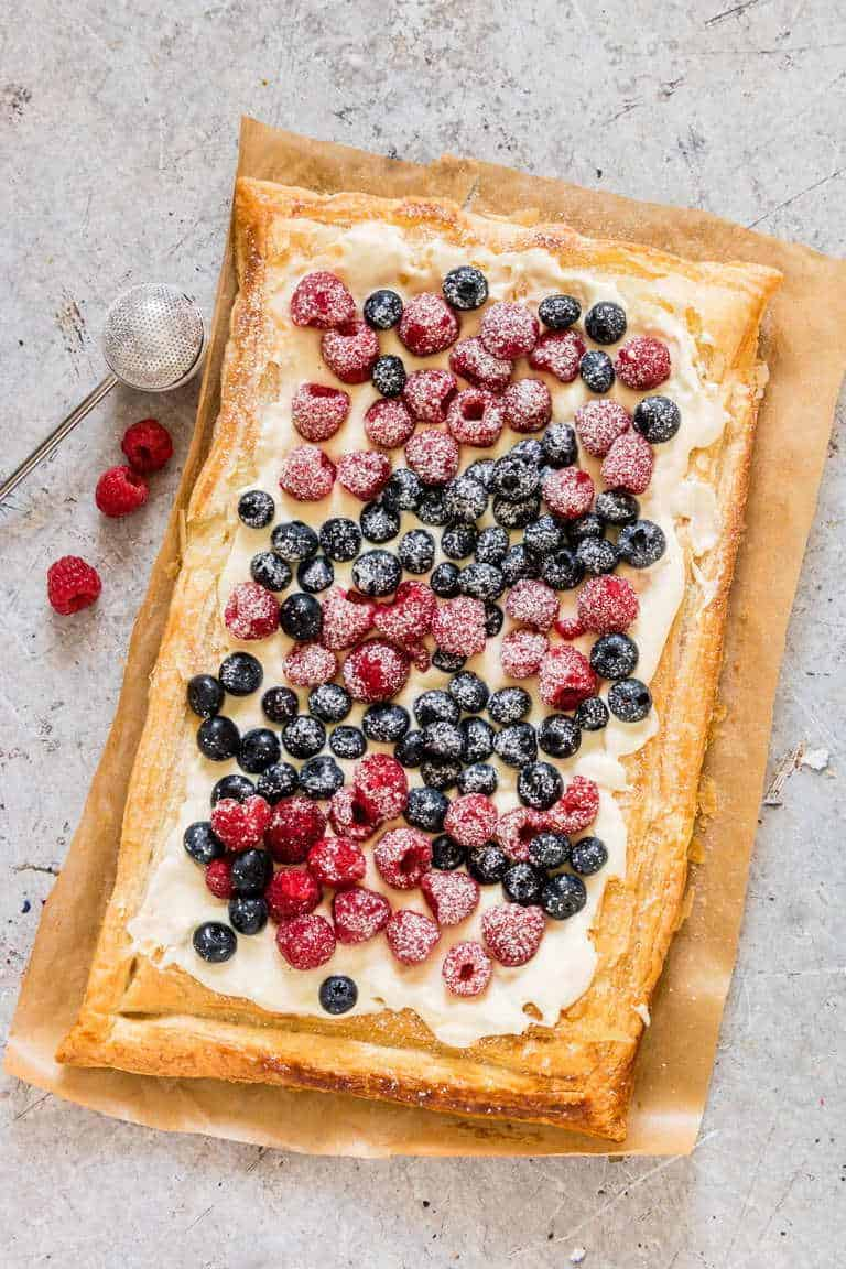 An overhead view of a whole puff pastry tart topped with cream cheese and berries on a white backdrop