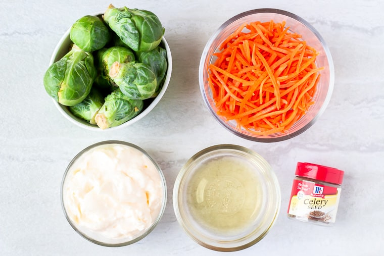 Ingredients for Brussels Sprouts Coleslaw in glass bowls over a white background