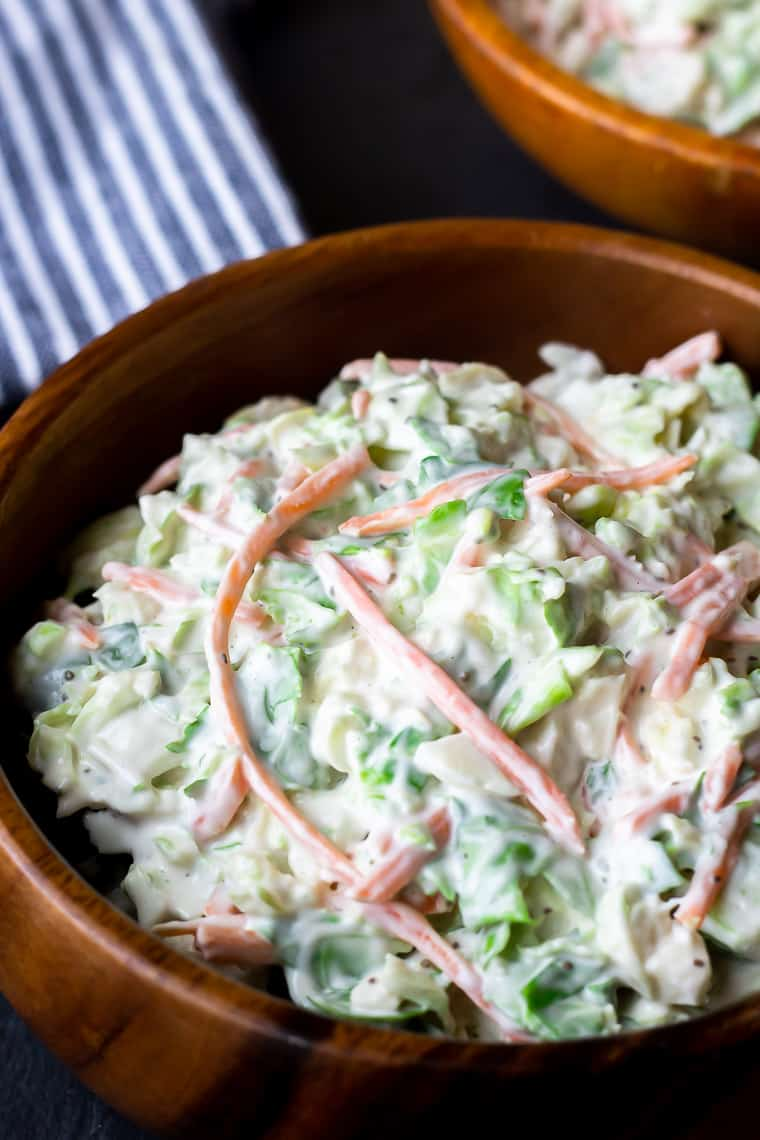 Close up of Brussels Sprouts Coleslaw in a wood bowl with a blue and white striped towel and an orange wood bowl in the background