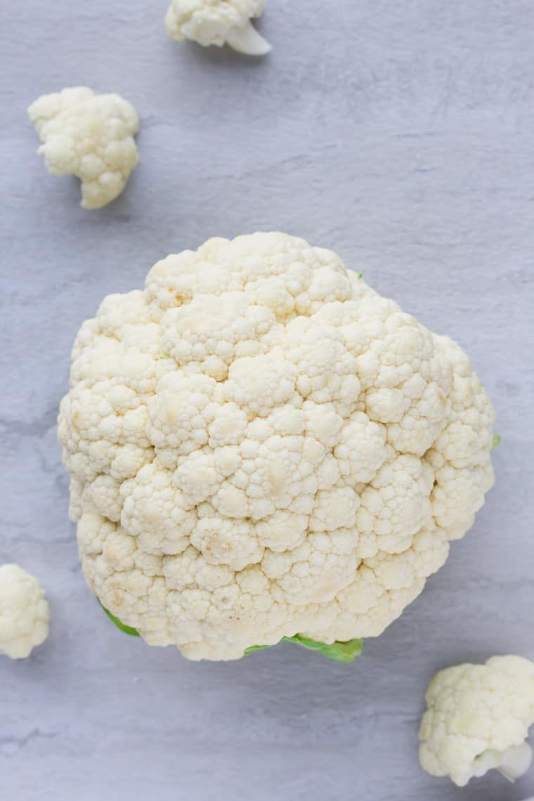 A head of cauliflower on a white background with florets around it