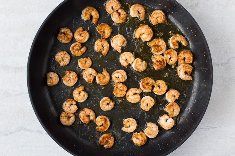 Cajun Seasoned Shrimp in a Black Skillet over a white background