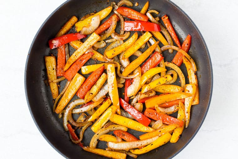 Peppers and onion cooking in a black skillet over a white background