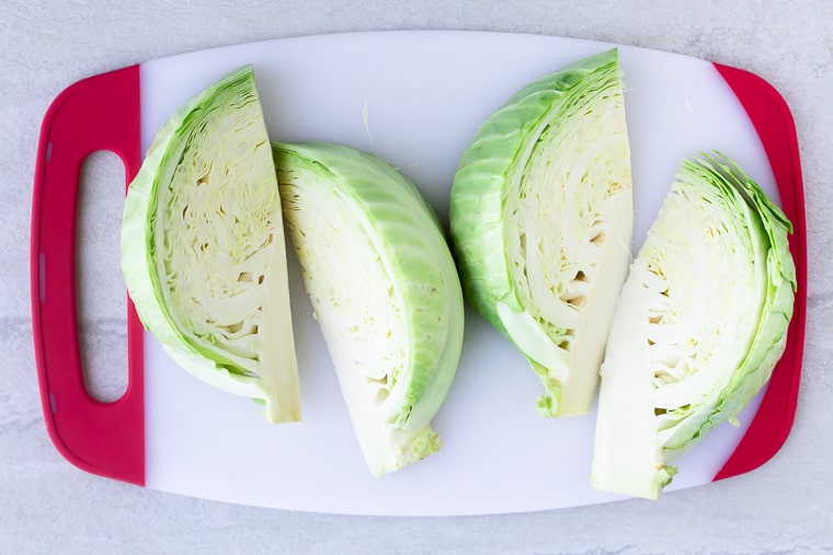 4 Cabbage Wedges on a white cutting board with red handles