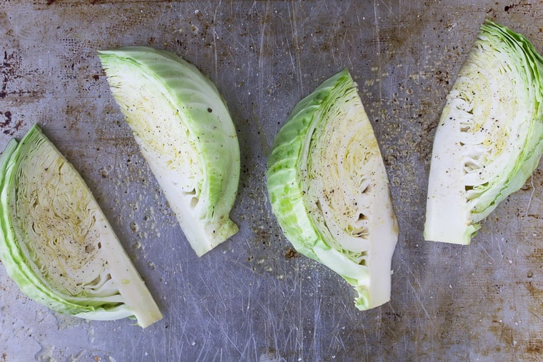 4 Cabbage Wedges on a sheet pan drizzles with oil and seasoned with salt and pepper