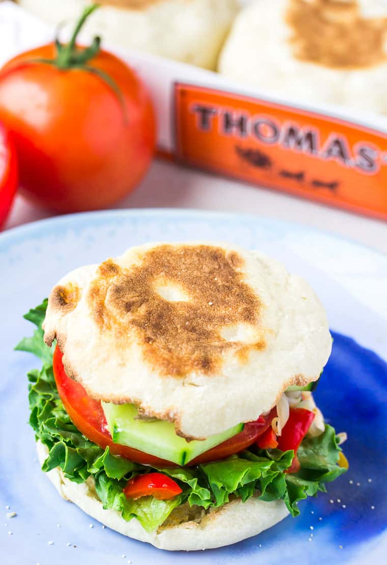 Veggie Sandwich on an English Muffin on a blue plate with tomatoes and thomas' english muffin pack in the background
