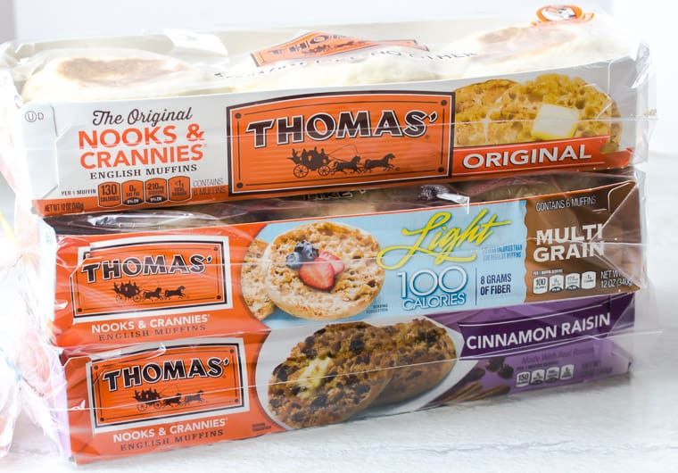 3 packages of Thomas' English Muffins on white background