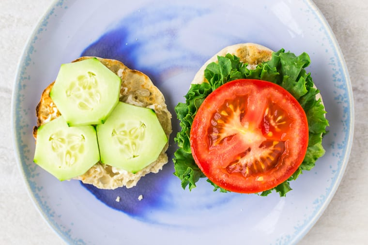 English muffin halves topped with lettuce, tomato, and cucumber on a blue plate over a white background
