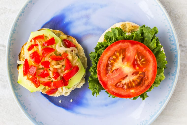 English muffin halves topped with lettuce, tomato, sprouts, red peppers and cucumber on a blue plate over a white background