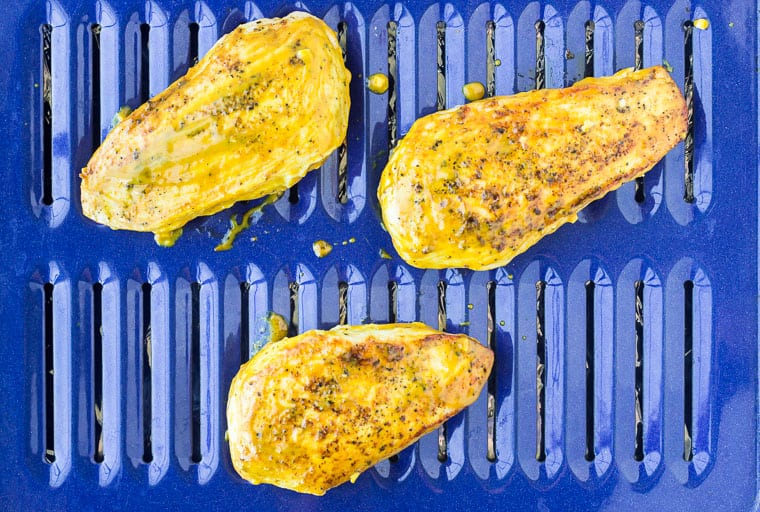 Chicken breasts on a blue broiler pan brushed with mustard sauce