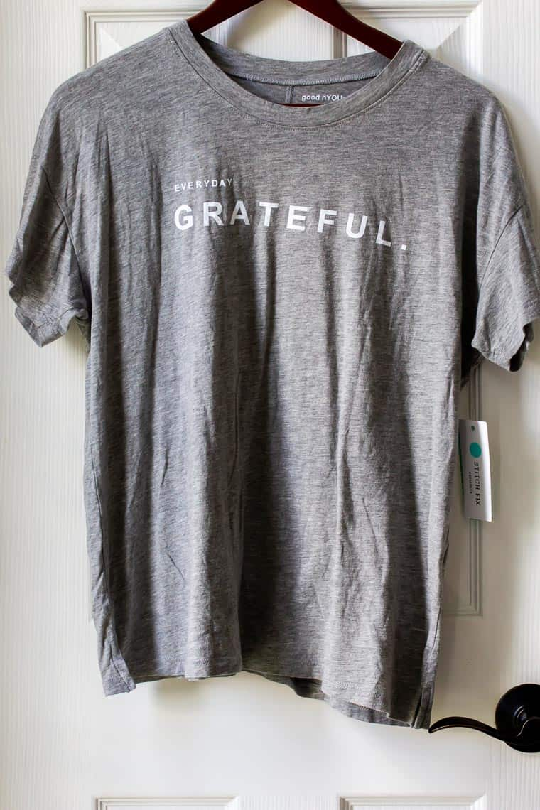 A gray tee shirt on a hanger in front of a white door