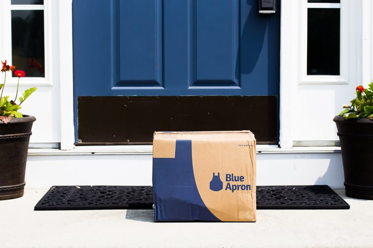 My July 2019 Blue Apron box on a front porch with a blue door with white trim