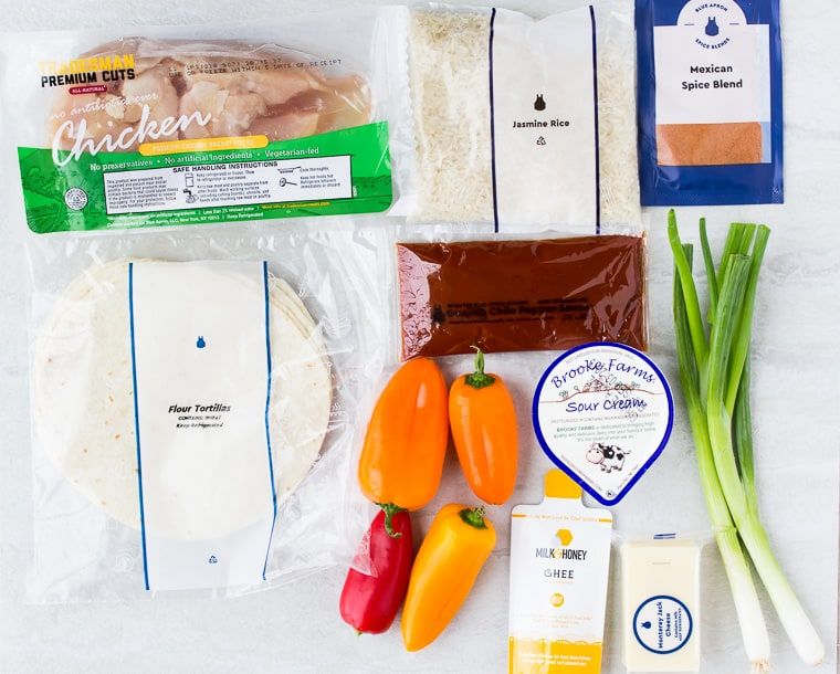 Ingredients for Blue Apron's Chicken Enchiladas spread out on a white background