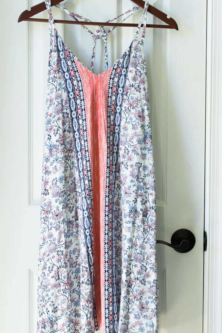 Blue and pink dress on a hanger in front of a white door