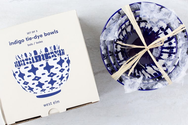 West Elm Indigo Tie Dye Bowls box with the blue and white bowls stacked next to it over a white background