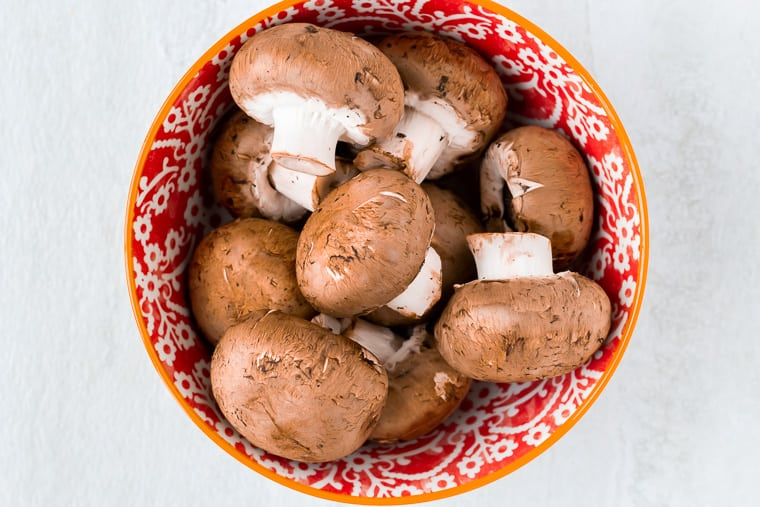Whole mushrooms in a red bowl on a white background