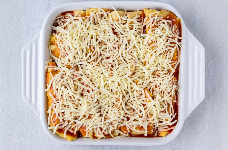 Enchiladas topped with sauce and cheese in a white casserole dish over a white background