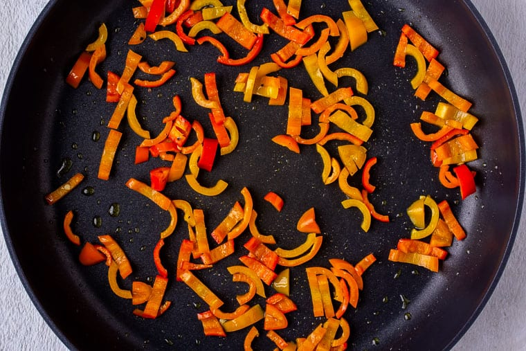 Sweet pepper slices cooking in a black skillet