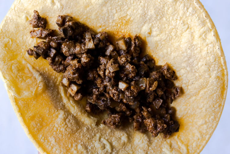 A corn tortilla filled with ground beef and mushrooms on a white background