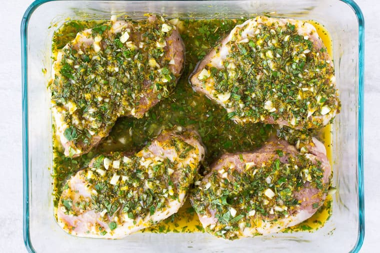4 pork chops and cuban marinade in a glass dish