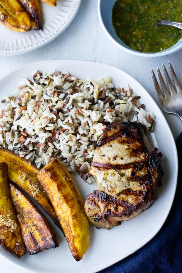 Grilled Cuban Pork Chops, sliced plantains, and coconut rice on a white plate with a white napkin, fork, small white plate with plantains, and light blue bowl with green sauce
