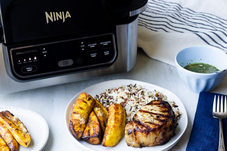 Grilled Pork Chops, plantains, and rice on a white plate in front of the Ninja Foodi grill with a blue napkin with a fork and a white and black napkin with a small light blue bowl of green sauce