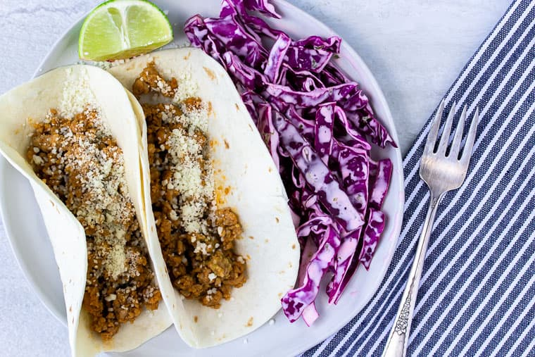 Blue Apron Tomatillo Pork Tacos on a white plate with a blue and white stripe napkin and fork over a white background