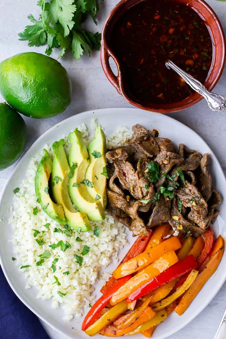 Keto beef fajitas bowls on a white background with an orange bowl of sauce, 2 limes and cilantro