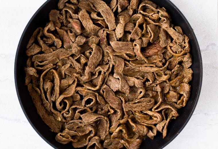 Cooked beef strips in a black skillet over a white background