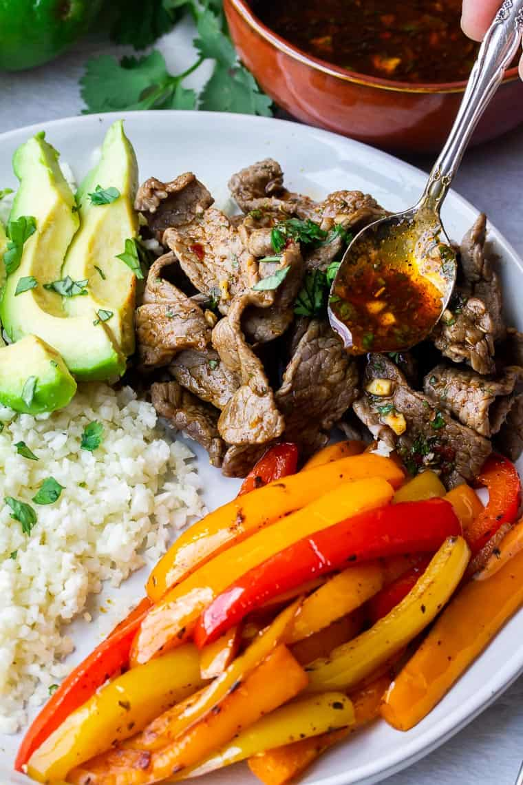 Sauce being spooned over a plate of beef fajitas with peppers, cauliflower rice, and avocado slices