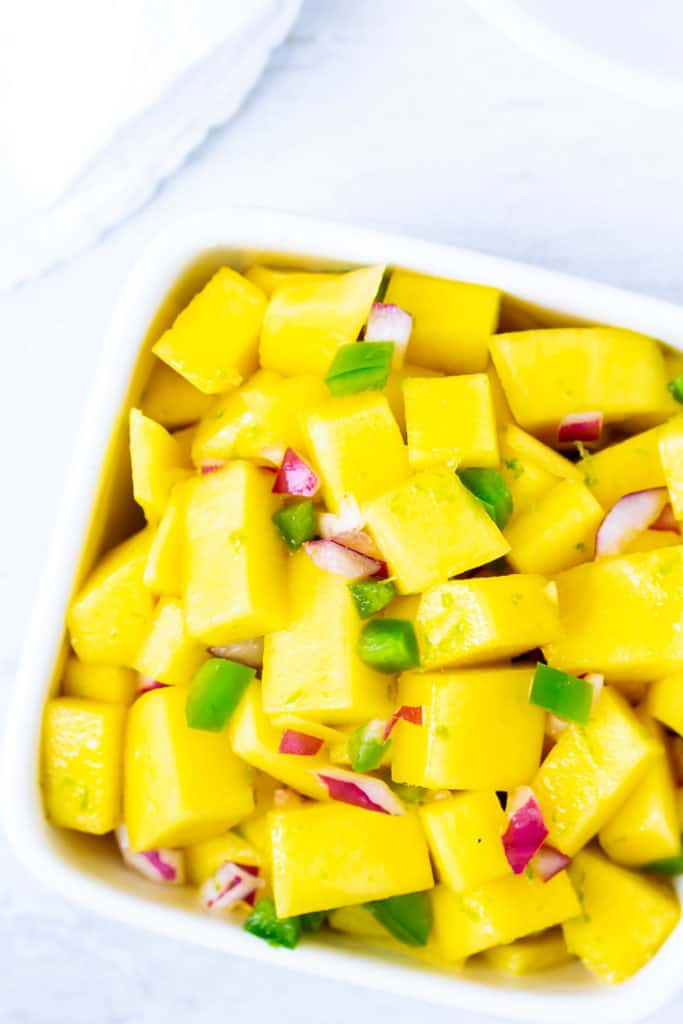 Overhead close up of spicy mango salsa in a white square bowl over a white background with a white napkin
