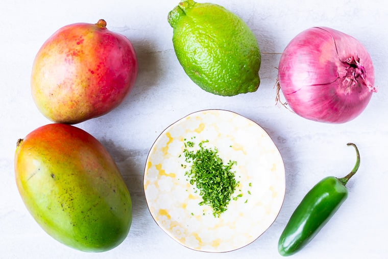 Ingredients for spicy mango salsa on a white background