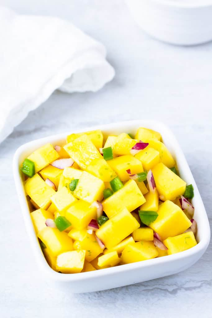 Spicy Mango Lime salsa in a square bowl on a white table with a white napkin and white bowl in the background