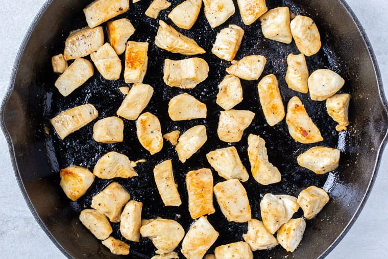 Pieces of cooked chicken in a black cast iron pan