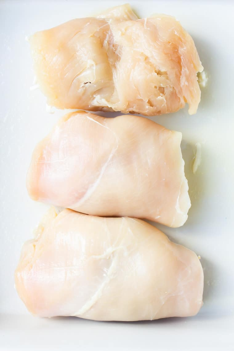 Three rolled up chicken breasts in a white baking dish