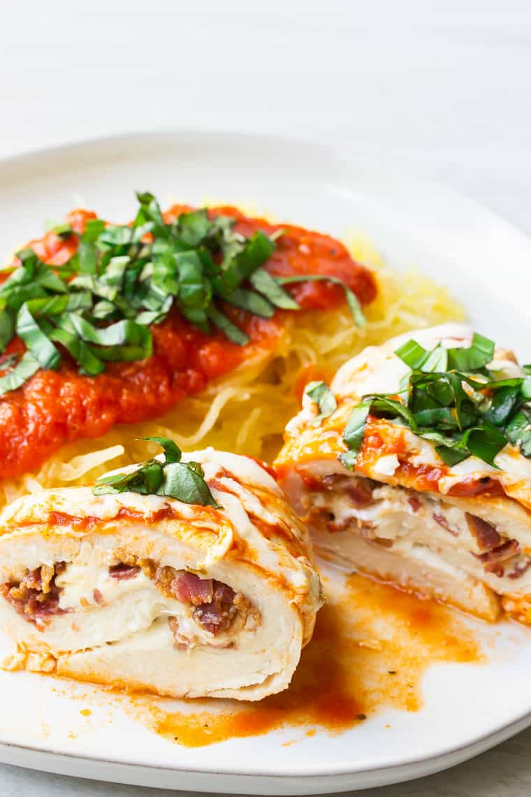 A chicken roll up cut in half on a white plate with spaghetti squash and fresh basil