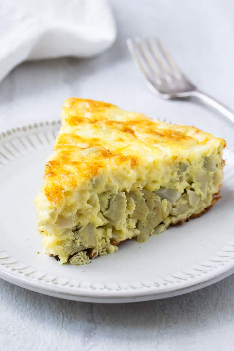 A slice of Artichoke Frittata on a cream color plate with a fork and white napkin in the background over white backdrop