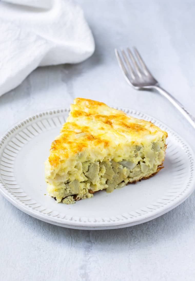 A slice of Artichoke and Shallot Frittata on a white plate with a fork and white napkin in the background