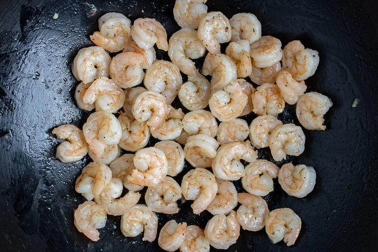 Cooked shrimp in a black skillet