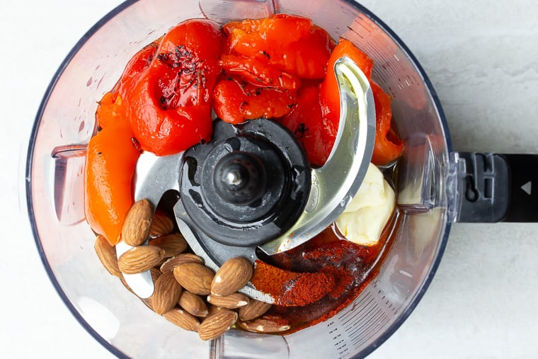 Peppers, almonds, and seasonings in the bowl of a food processor with a blade over a white background