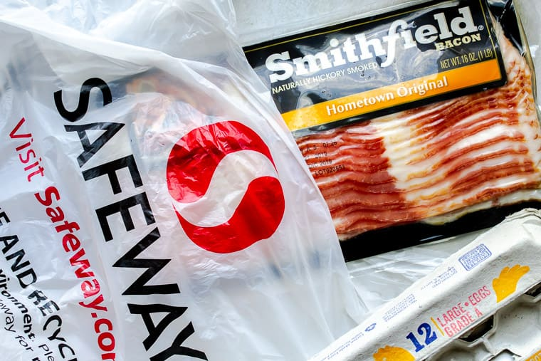 Safeway bag with a package of bacon sticking out of it and part of an egg carton off to the side