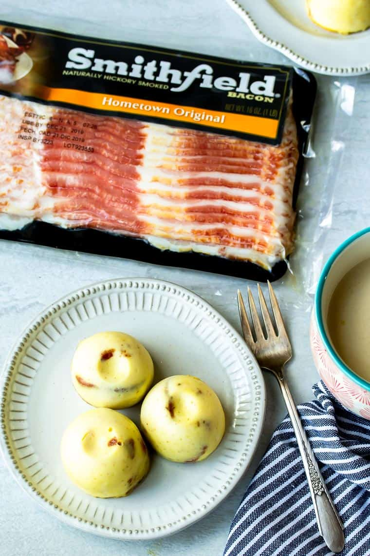 3 Instant Pot Egg Bites on a white plate with a fork, cup of tea, striped napkin, and package of bacon in the background all over a white backdrop