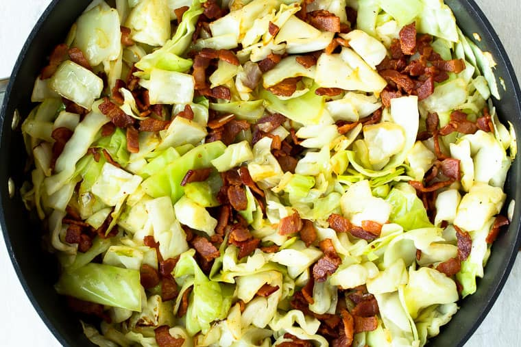 Fried cabbage and bacon in a black skillet