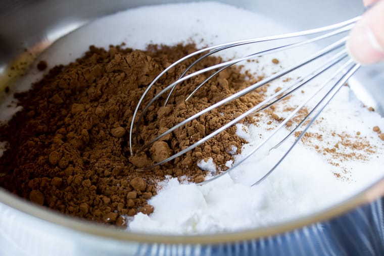 Close up of a silver saucepan with cocoa powder, sugar, and a whisk in it