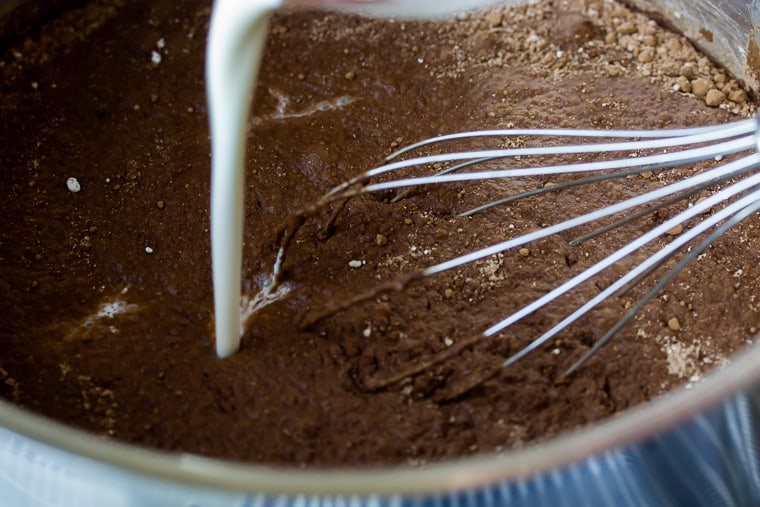 Cream being poured into a chocolate mixture in a sauce pan with a whisk