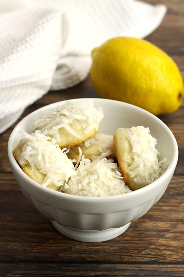 Lemon Coconut Snowball Cookies in a white bowl on a wood table with a lemon and white towel in the background