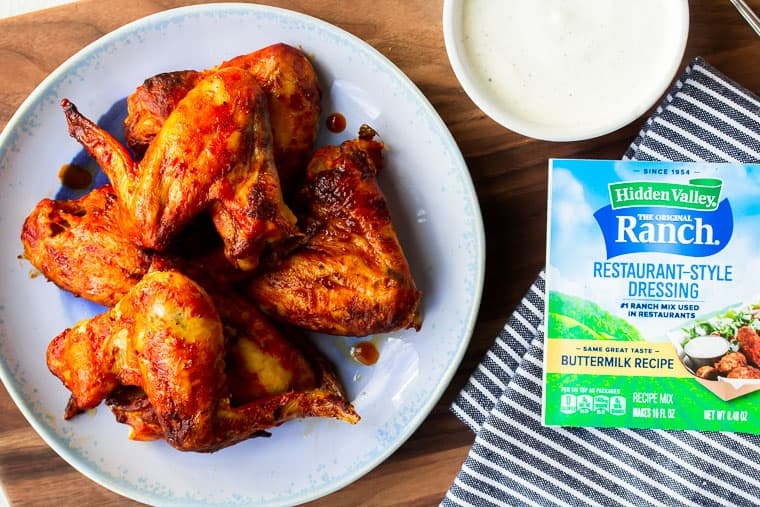 Chicken wings on a blue plate over a wood cutting board with a packet of Ranch, a bowl of Ranch, and a blue and white towel