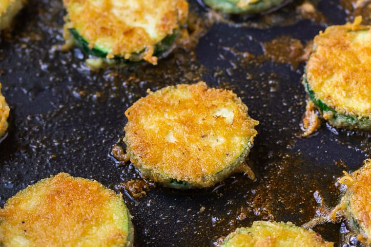 Close up of a slice of zucchini frying in a black skillet
